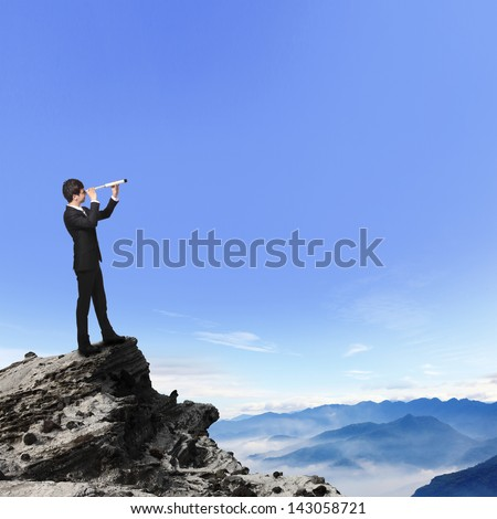 business man looks through a telescope on the top mountain. concept for business, leadership, success,