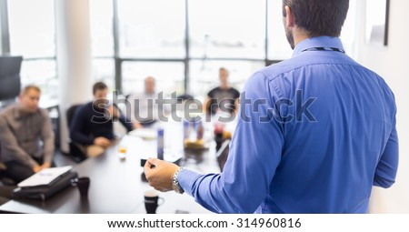 Business man making a presentation at office. Business executive delivering a presentation to his colleagues during meeting or in-house business training, explaining business plans to his employees.  #314960816
