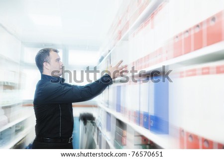 business man male adult in archive library looking and searching for book and documents representing storage and education concept