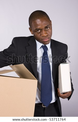 Business man moving out with a cardboard box and a book