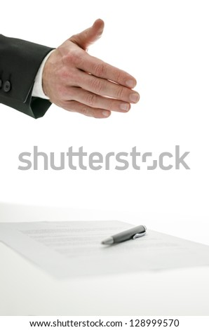Business man offering a handshake over a signed contract.  Isolated over white background.