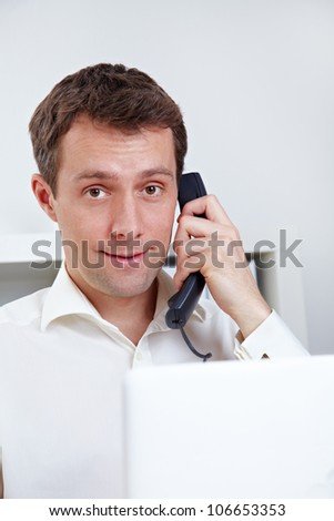 Business man on the phone with laptop at desktop