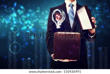 Business man opening box with an idea light bulb on blue technology background