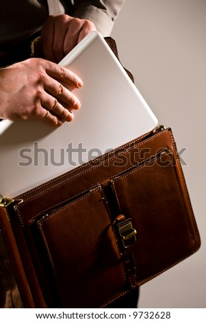 Business man opening elegant brown leather briefcase to take out laptop computer.