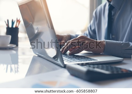 Business man or accountant working on laptop computer with business document, graph diagram and calculator on office table