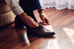 Business man or groom dressing up with classic elegant leather shoes. Groom wearing on wedding day, tying the laces on his shoes.