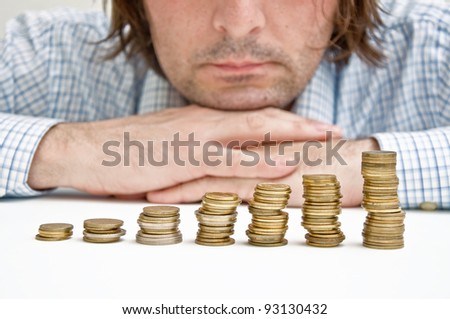 Business man over coin stack. Businessman siting at the table and thinking about possible money investments. - stock photo