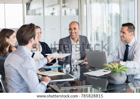 Business man passing over documents to leader during meeting. Businessman passing agreement to the business partner in conference room. Group of businessmen and businesswomen working together.