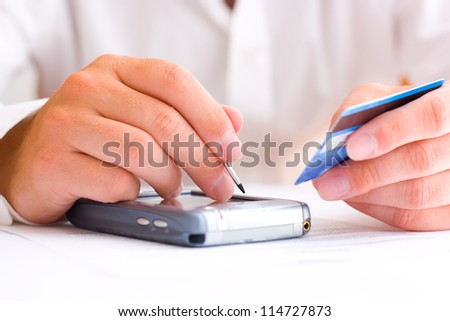 Business man paying with a credit card using a PDA