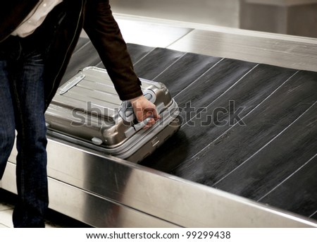 Business man picking up metal suitcase from conveyor belt at airport