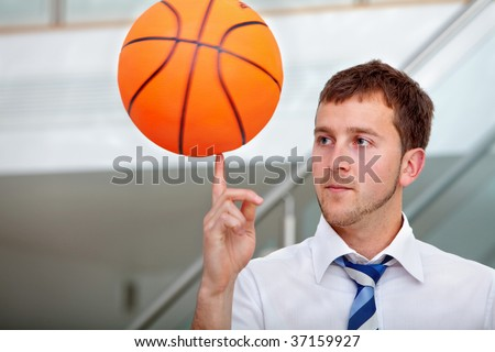 Business man playing with a basketball at the office