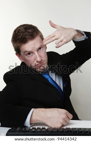 business man point his fingers to his head as if he about to shoot himself