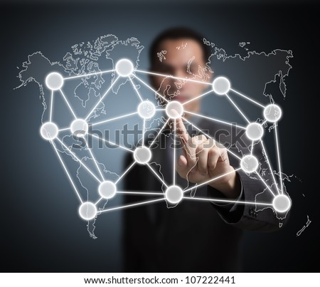 business man pointing at global network on world map - stock photo