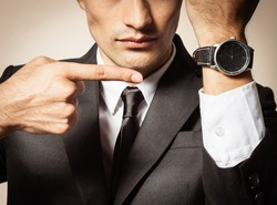 Business man pointing at the time. Running late.