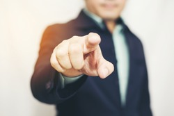 Business man pointing finger soft focus background