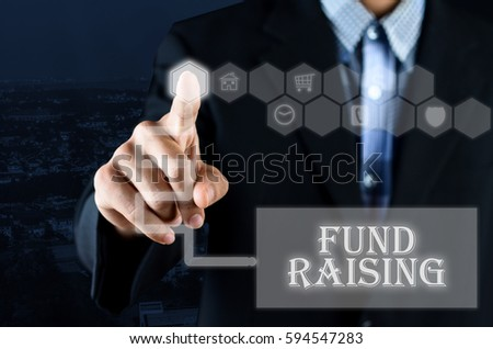 Business man pointing hand on transparent screen button with word Fund Raising