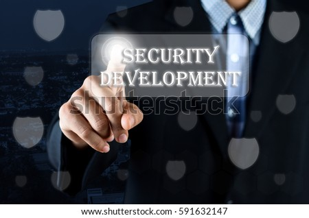 Business man pointing hand on transparent screen with Security symbol and text written Security Development