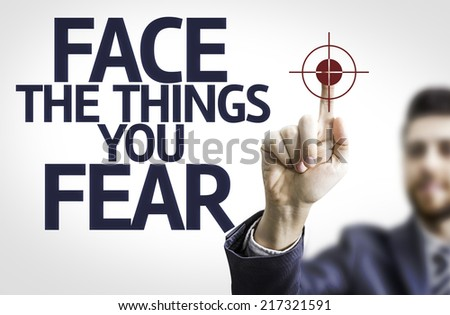 Business man pointing to transparent board with text: Face the Things you Fear
