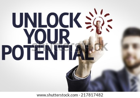 Business man pointing to transparent board with text: Unlock Your Potential