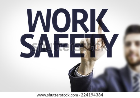 Business man pointing to transparent board with text: Work Safety
