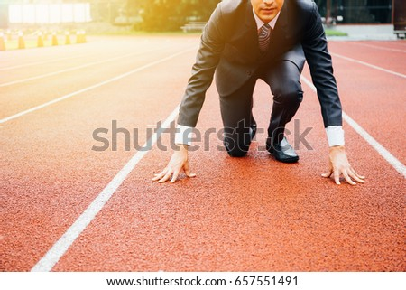 Business man preparing to run on the competition running track
