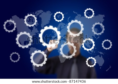 business man push a industrial gear touch screen button with world map background