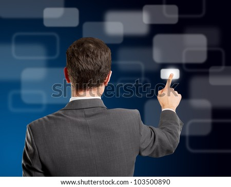 Business man push the button on virtual touch pad from behind