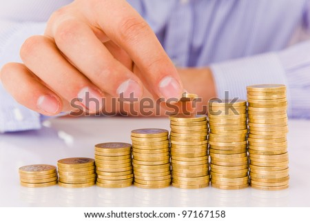Business man put coins to money staircase