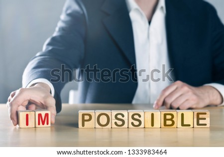 Business man puts away first two letters from the word impossible, so it becomes possible; management or solution finding concept, blue toned with ligth flare #1333983464