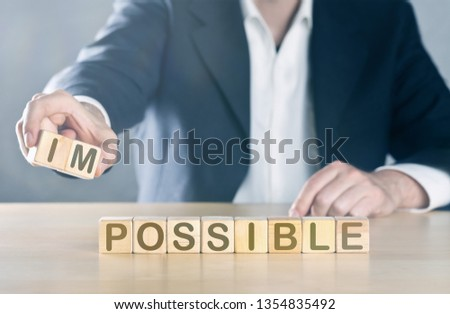 Business man puts away first two letters from the word impossible, so it becomes possible; management or solution finding concept, blue toned with ligth flare #1354835492