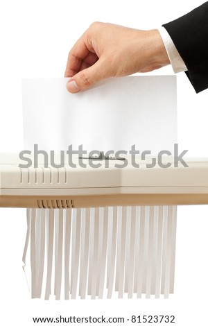 Business man puts single piece of paper in shredder; empty paper with copyspace - stock photo