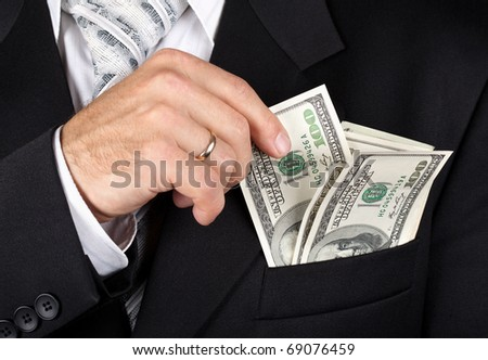Business man putting dollar banknotes into his pocket