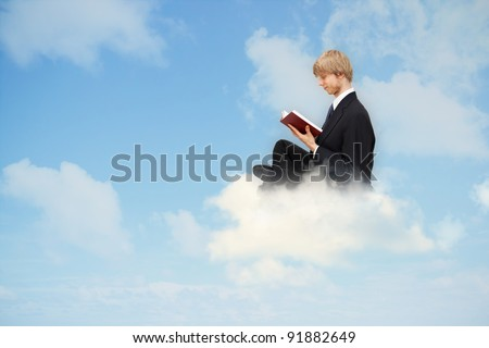 Business man reading book on the cloud