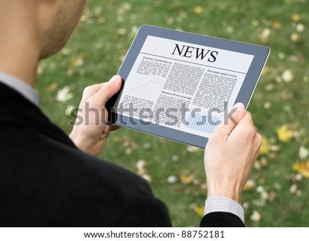 Business man reading news on digital tablet at park.