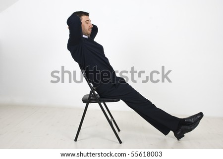 Business man  resting on chair in an empty room,he sitting with hands under head looking down and thinking