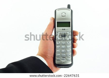 Business man's hand holding a cordless phone isolated on white