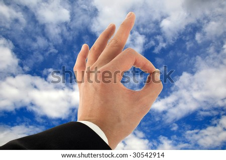 Business man's hand signing okay in the sky