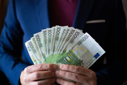 Business man's hands shows a bunch of money. Business man. Close-up of caucasian man's hands in blue jacket shows banknotes of 100 euro