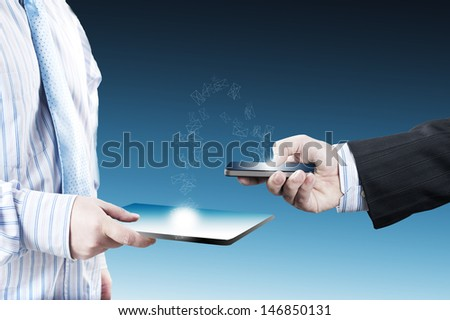 Business man sending email from smart phone to tablet PC - stock photo