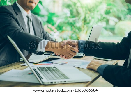Business man shaking hand after signing contract with cooperator, Team work concept, Dealing complete #1065966584