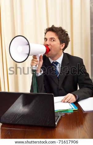 Business man shouting in megaphone and sitting on chair in office