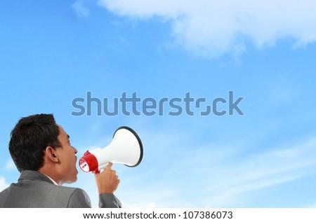 business man shouting using megaphone under the blue sky