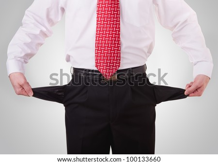 business man showing his empty pockets demonstrating he has no money