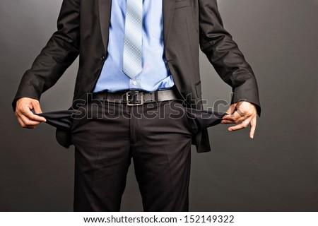 Business man showing his empty pockets  on gray background Stock photo ©