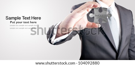 "Business man showing metal jigsaw puzzle piece with ""SUCCESS"" wording. Concept for business strength and success."