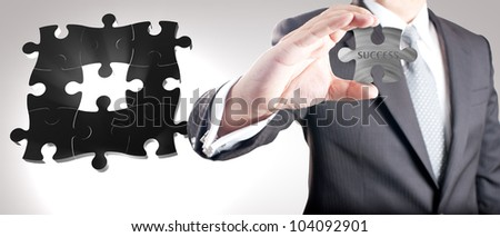 "Business man showing missing metal jigsaw puzzle piece with ""SUCCESS"" wording. Concept for business strength and success."
