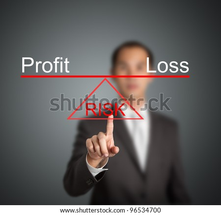 business man showing profit or loss is on balance on sharp point of risk base