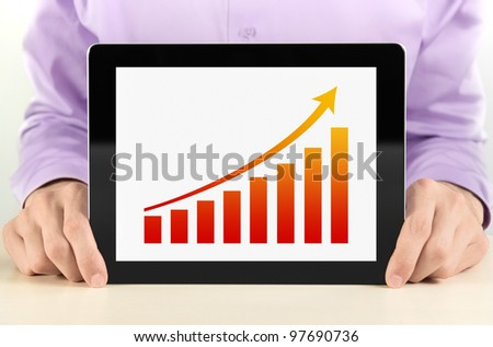 Business man showing tablet pc with success growth graph on screen.
