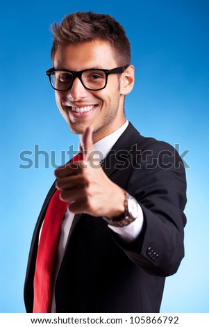 Business man shows thumbs up ok gesture on blue background