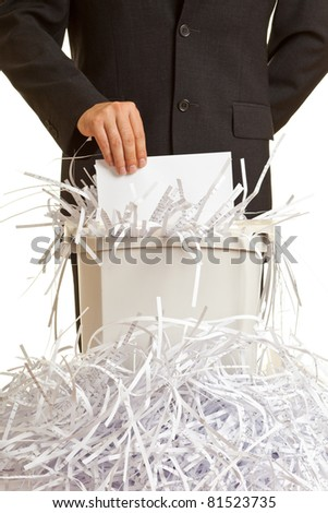 Business man shredding confidential documents at overflowing shredder - stock photo